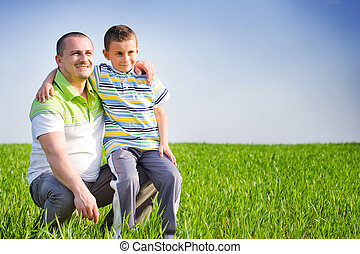 Father and son having good time outdoor - Father and son...
