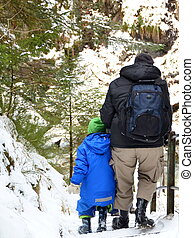Father and son hiking in the snow