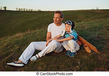 Father and son i sitting on the grass at sunset in nature.