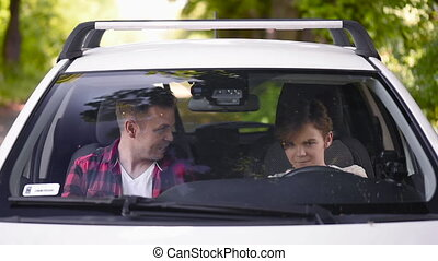 Caring parent teaching his son how to drive car. Father passes on knowledge to teenage son. Man and teen boy spending time together, family.