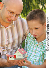 father and son in early fall park. they looking at wendy house. focus on son\'s face. wendy house in out of focus