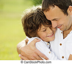 Father and son in nature - Father and son hugging and...