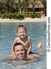 Father and son in outside swimming pool at a tropical resort