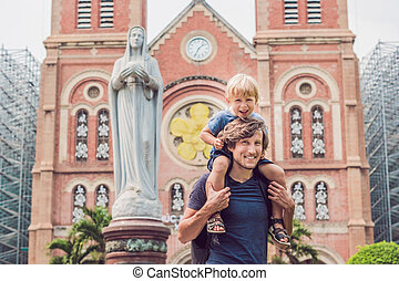Father and son in the background Notre dame de Saigon Cathedral, build in 1883 in Ho Chi Minh city, Vietnam