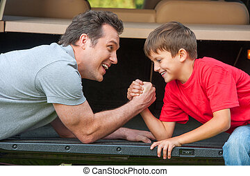Father and son is wrestling at the opened car boot. Smiling...