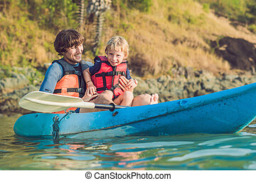 Father and son kayaking at tropical ocean.