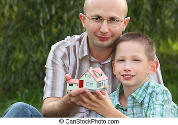 father and son keeping in their hands wendy house and looking at camera. focus on father\'s face. wendy house in out of focus.