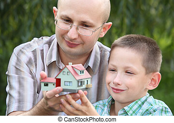 father and son keeping in their hands wendy house. focus on father\'s face. wendy house in out of focus.