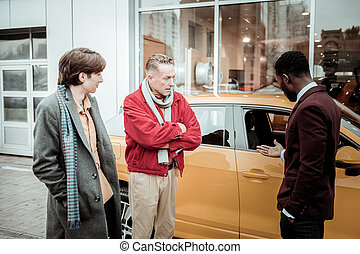 Father and son listening to sales manager while hopping for car