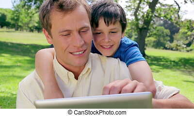 Father and son looking at an ebook in the countryside