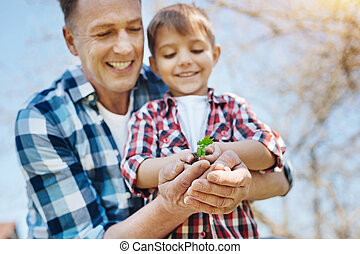 Father and son looking at small plant in their hands