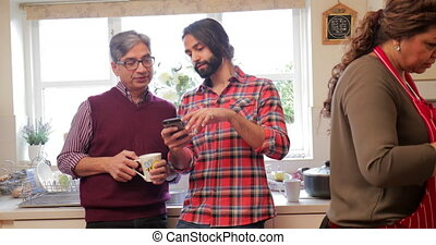 Father and Son Looking at Smart Phone - Mid adult man is...
