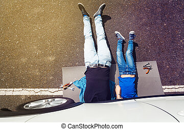 Father and son lying under auto doing repair work