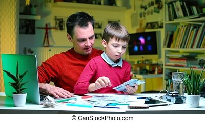 Father and son make a calculation of the family budget.