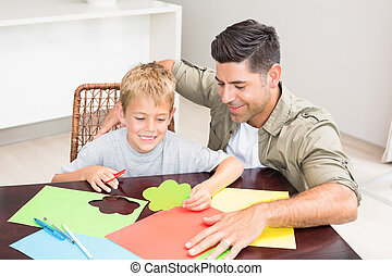 Father and son making paper shapes together at the table