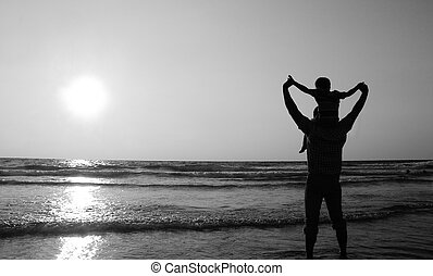 father and son on a walk by the sea at sunset. Black and white photo.