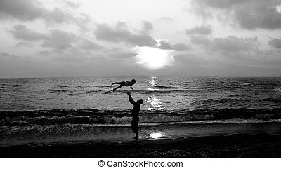 father and son on a walk by the sea at sunset