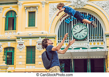 Father and son on background Saigon Central Post Office on blue sky background in Ho Chi Minh, Vietnam. The inscription on the Vietnamese post office
