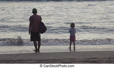 Father and son on beach at sunset - Father and son on the...