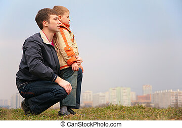 father and son on grass. city