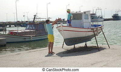 Father and son on the docks with boats