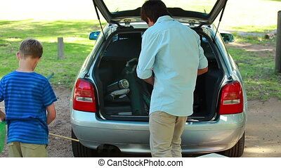 Father and son placing things in the trunk of the car