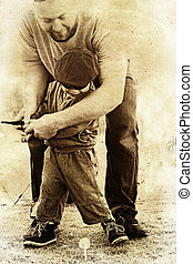 father and son play golf. - father teaches his toddler son...