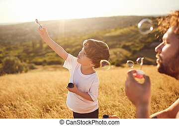 Father and son play with soap bubbles in nature