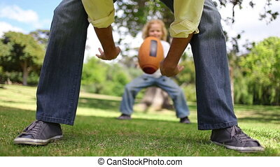 Father and son playing american football in a park