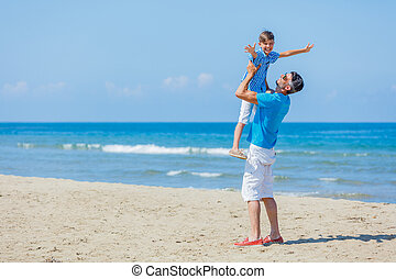 Father and son playing at beach together.