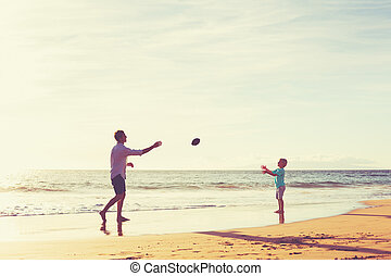 Father and Son Playing Catch Throwing Football on the Beach...