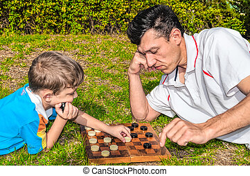 Father and son playing checkers on the grass