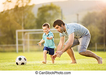 Father and son playing football - Young father with his ...