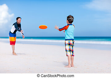 Father and son playing frisbee at beach