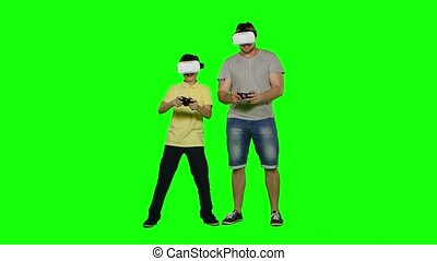 Father and son playing in virtual reality glasses. Green screen