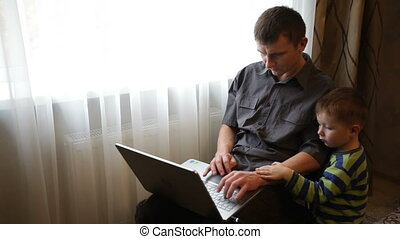 Father and son playing on laptop in game