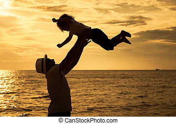 Father and son playing on the beach at the dawn time. ...