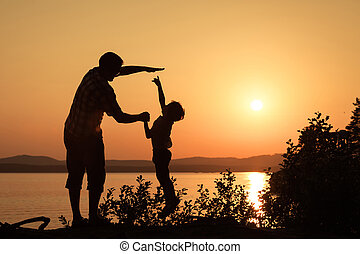 father and son playing on the coast of lake