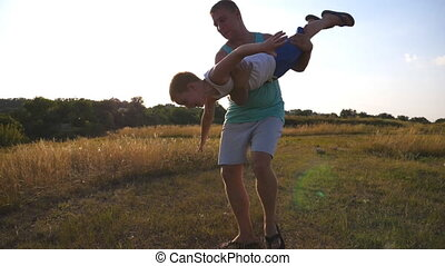 Father and son playing on the field at sunny summer day. Happy daddy holding and rotates his little child in hands. Boy imagines he flies like a plane. Happy family spending time outdoor. Slow motion