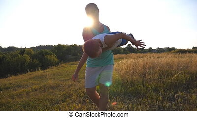 Father and son playing on the field at sunset. Happy daddy rotates his little child in hands. Boy imagines he flies like a plane. Happy family spending time outdoor. Active lifestyle. Slow motion