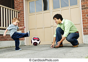Father and son playing soccer - Father teaching son to play...