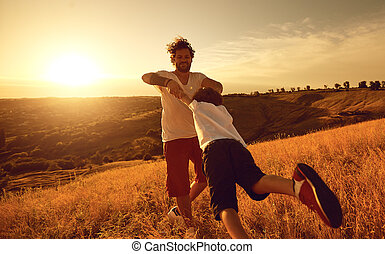 Father and son playing together in nature at sunset.