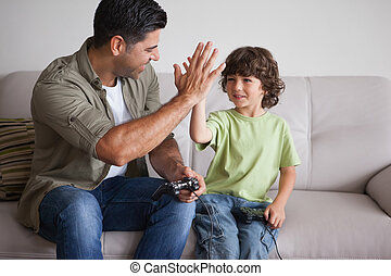 Father and son playing video games in living room - Cheerful...