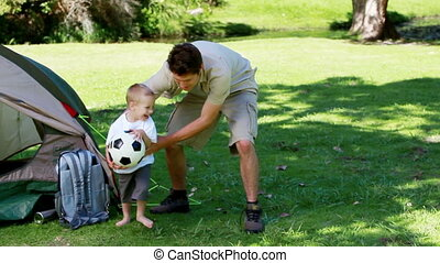 Father and son playing with a football