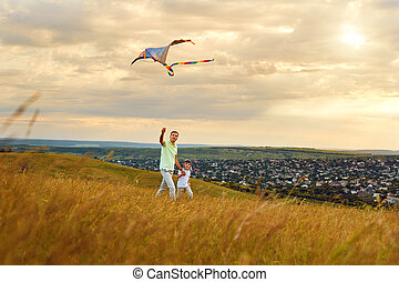 Father and son playing with a kite in nature.