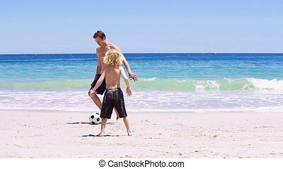 Father and son playing with a soccer ball on the beach