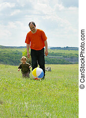 father and son playing with ball outdoors