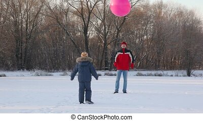 father and son plays with air-balloon in snowfield - father...