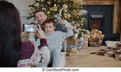 Father and son posing for smartphone camera while mother ...