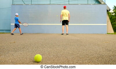 Father and son practice tennis at training wall. Hobby players with racket and ball playing on the court